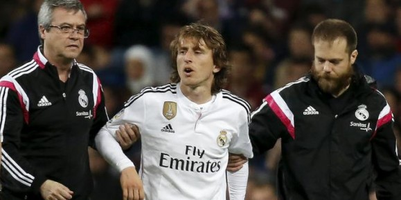 Real Madrid's Luka Modric leaves the pitch after an injury during their Spanish First Division soccer match against Malaga at Santiago Bernabeu stadium in Madrid